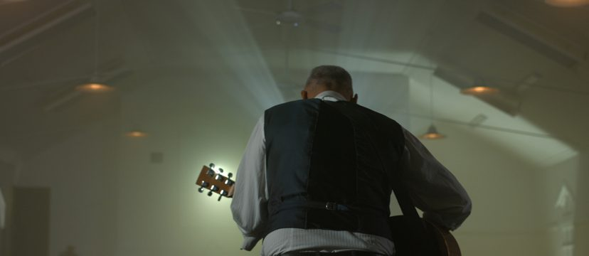 New Zealand musician Ryan Edwards playing guitar in a dark room